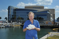 NSU Oceanographic Center (OC) professor Richard Spieler, Ph.D., holds a piece of coral in front of NSU's Center for Excellence for Coral Reef Ecosystems Science Research Facility.